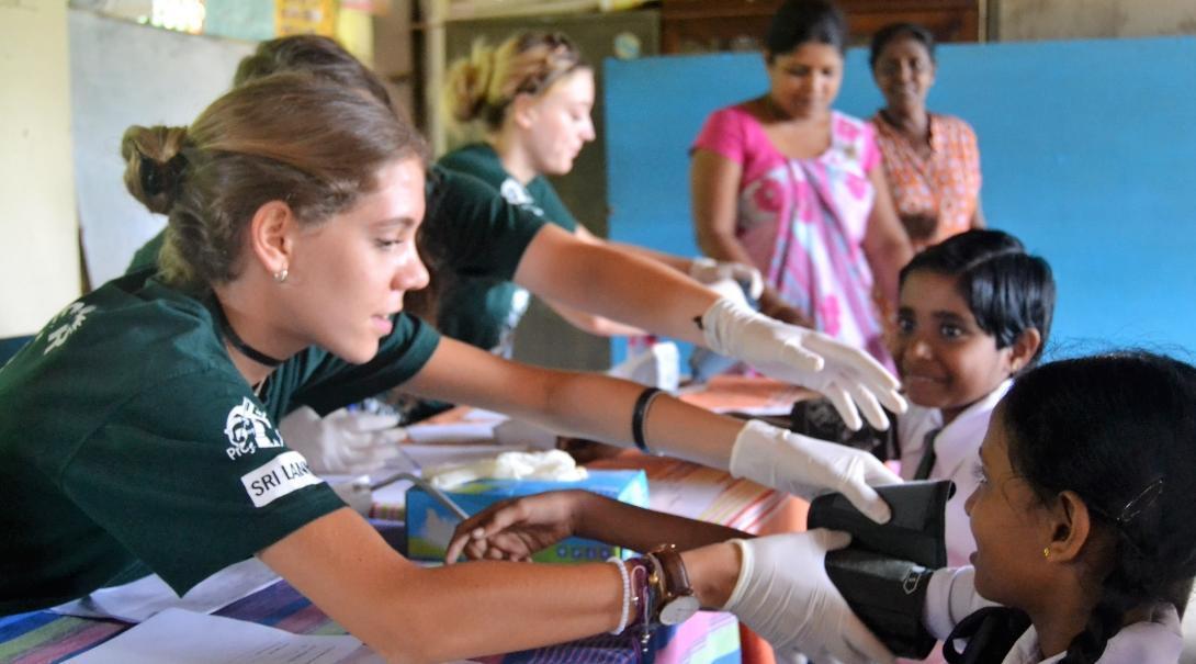 Pasante de medicina en Sri Lanka tomando la presión de una niña.